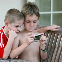 two young brothers playing ipod game