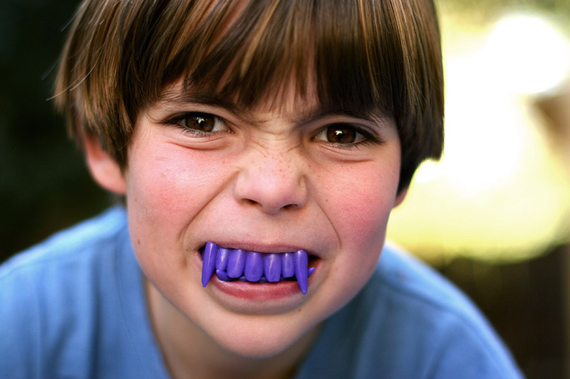 young boy with purple vampire teeth