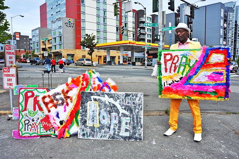 seattle man holding pray sign