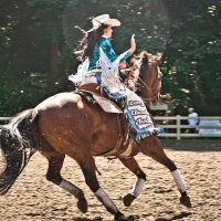 ellensburg rodeo princess on horse waving